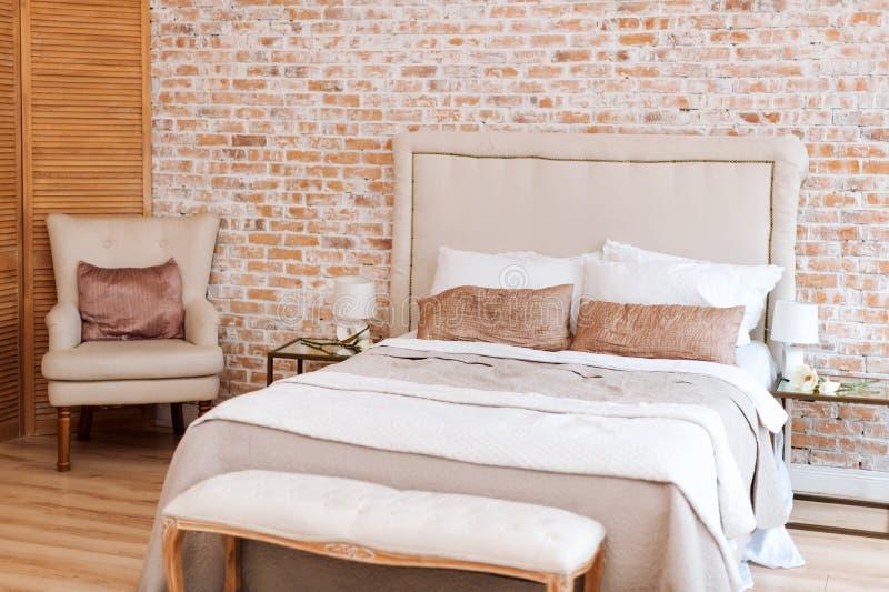 Dormitorio hermoso del desván con la cama y butaca cerca de la pared de ladrillo foto de archivo libre de regalías