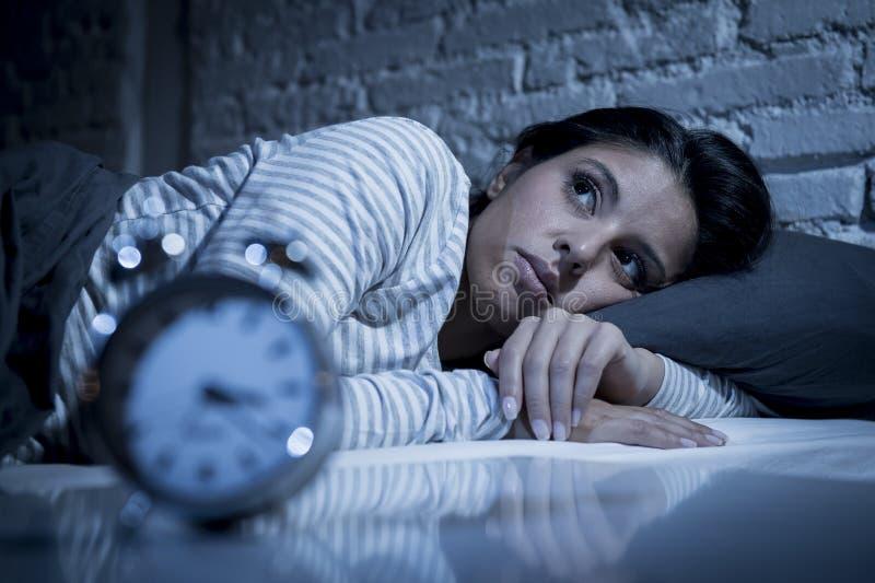 Dormitorio hispánico de la mujer en casa que miente en cama tarde en la noche que intenta dormir insomnio sufridor imágenes de archivo libres de regalías