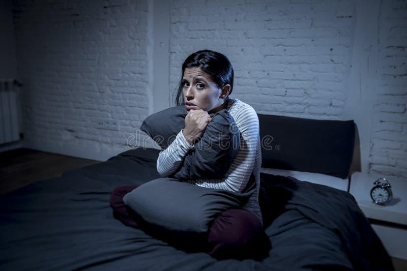 Dormitorio hispánico de la mujer en casa que miente en cama tarde en la noche que intenta dormir insomnio sufridor fotografía de archivo