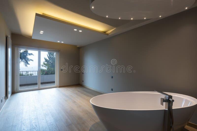 Dormitorio moderno con la bañera, apartamento de lujo fotografía de archivo libre de regalías
