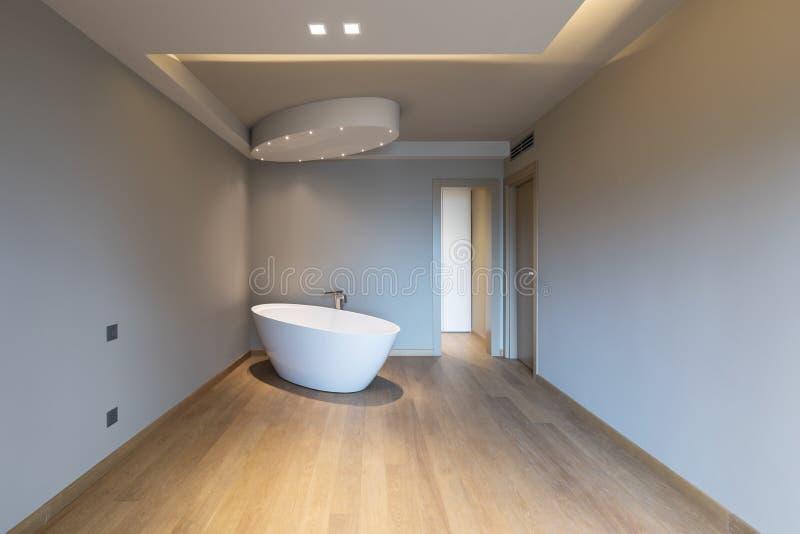 Dormitorio moderno con la bañera, apartamento de lujo foto de archivo libre de regalías