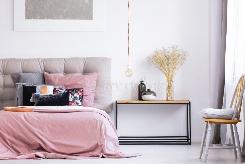 Dormitorio moderno con la silla anaranjada foto de archivo