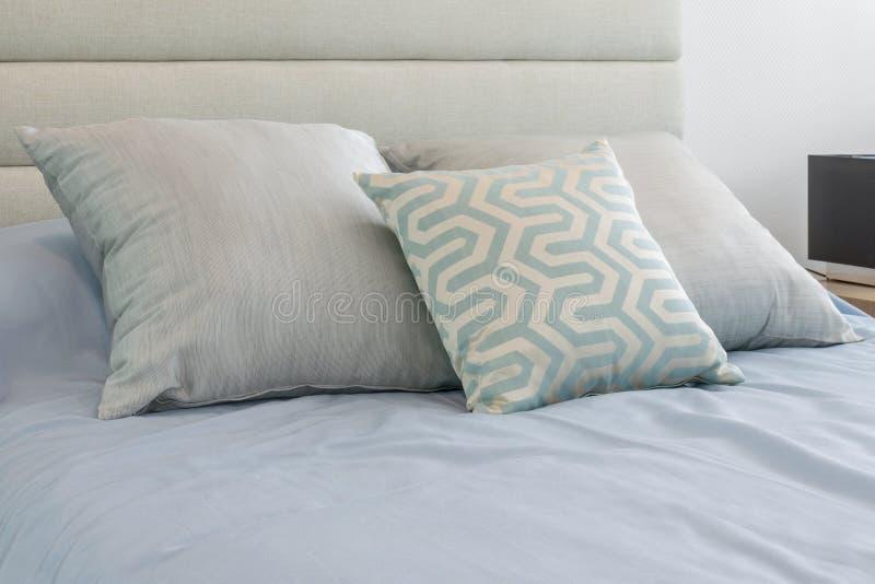 Dormitorio moderno con las almohadas suaves cómodas en la cama azul clara en casa imagen de archivo