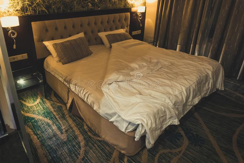 Dormitorio moderno de lujo del estilo Cama matrimonial grande en un pequeño dormitorio por la tarde del sitio luz de luces de la  imagenes de archivo