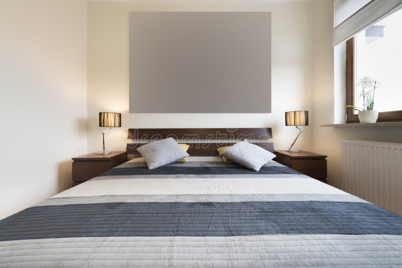 Dormitorio moderno en el acabamiento beige fotografía de archivo libre de regalías