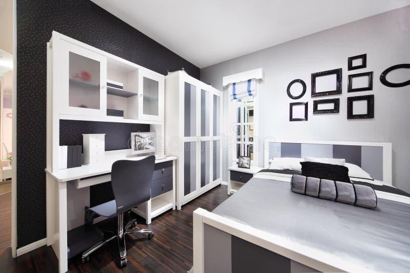 Dormitorio negro-blanco elegante con la cama matrimonial foto de archivo libre de regalías