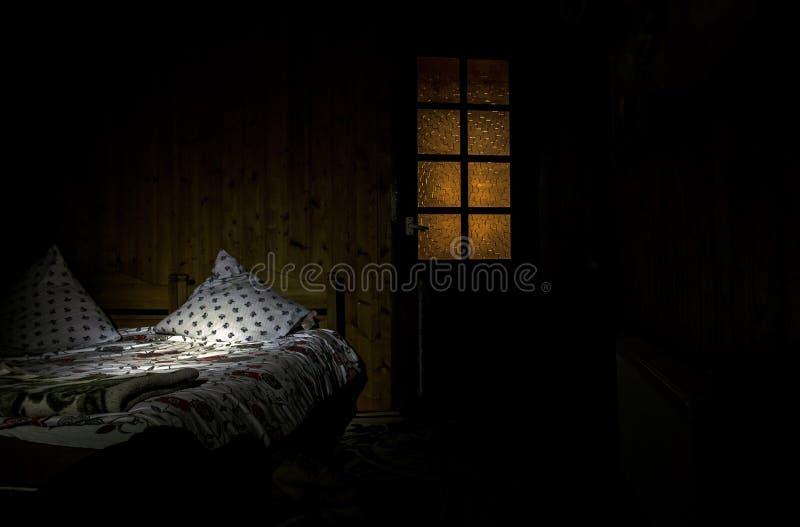 Dormitorio oscuro con las luces surrealistas de la cama y de las almohadas y puerta de madera con la ventana fotos de archivo