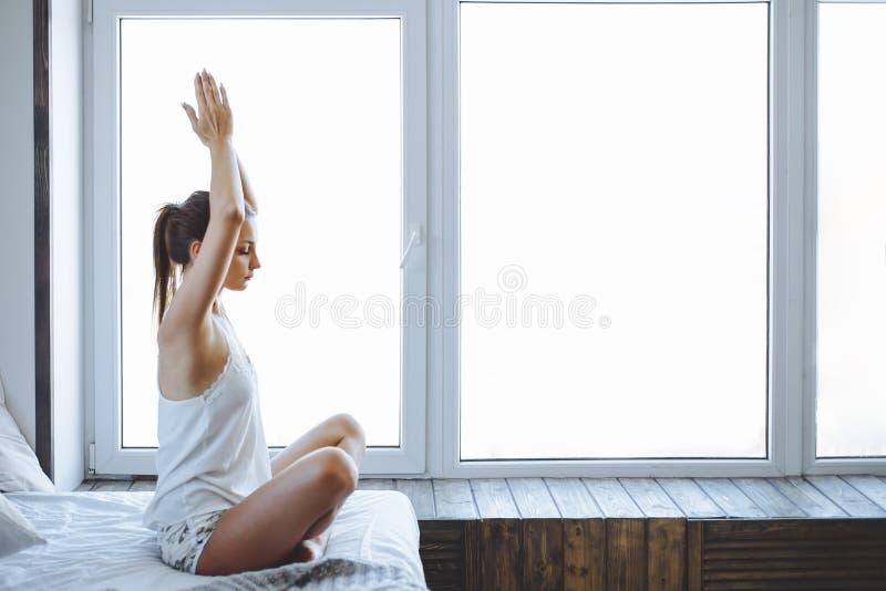 Dormitorio practicante de la yoga de la mujer deportiva joven en casa después de despertar fotos de archivo libres de regalías