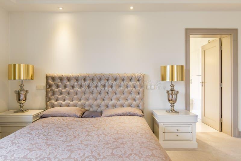 Dormitorio principal elegante con la cama foto de archivo libre de regalías