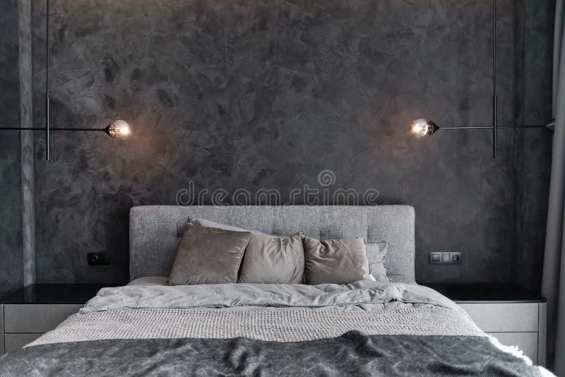 Dormitorio principal para un hombre elegante solo, soltero Sitio moderno con los interiores grises de moda, gigante grande y las  fotos de archivo libres de regalías