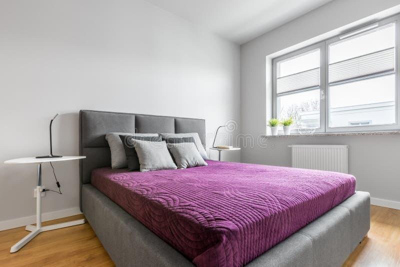 Dormitorio simple con la cama tapizada imagen de archivo