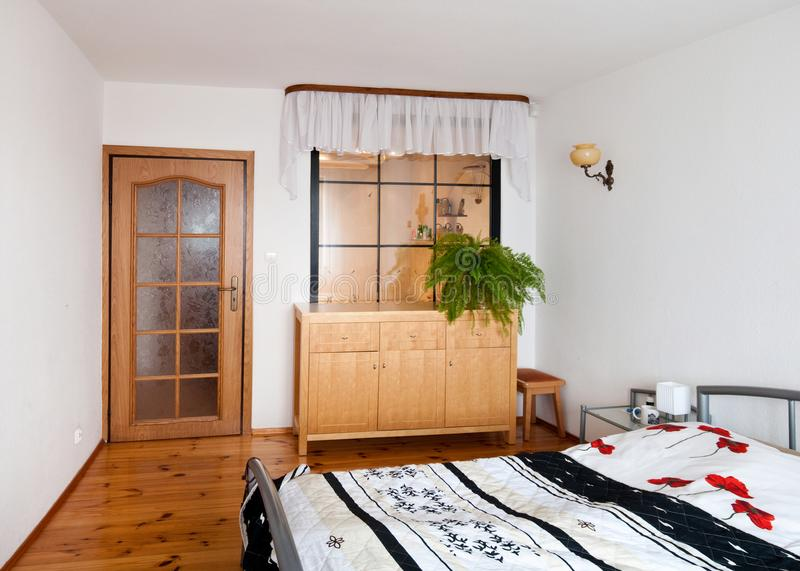 Dormitorio simple elegante con la cama matrimonial y el suelo de madera fotos de archivo libres de regalías