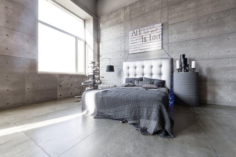 Dormitorio vacío moderno en estilo del desván con colores grises y árbol de navidad hecho a mano de madera con los presentes fotografía de archivo