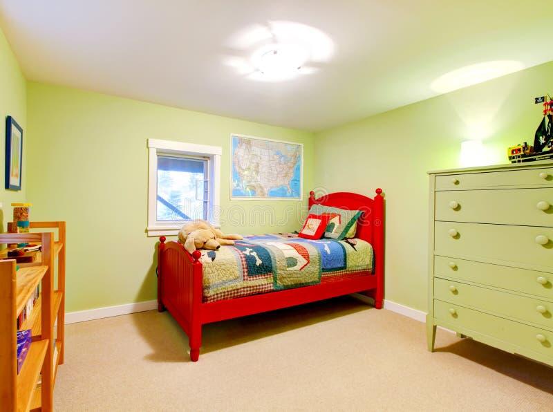 Dormitorio verde de los cabritos de los muchachos con la cama roja. imagen de archivo
