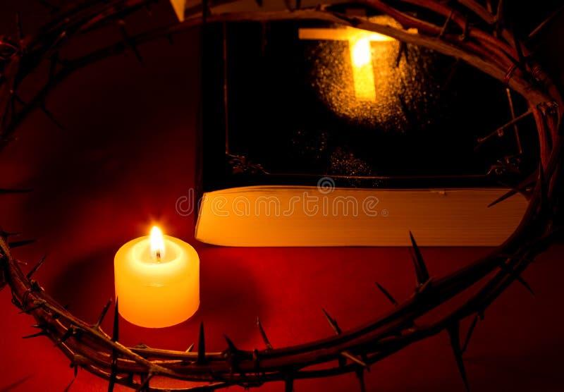 Dornenkrone von Jesus Christ setzte an die Bibel neben einer Kerze stockfotografie