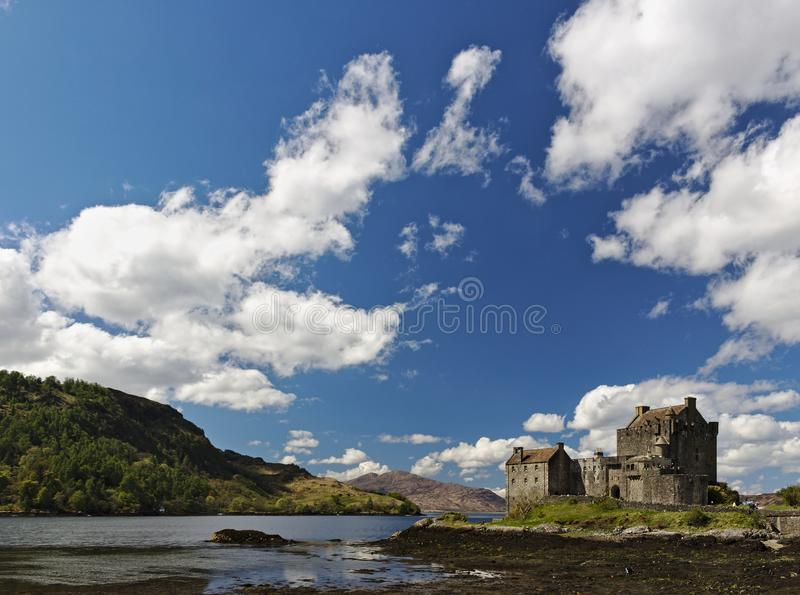 Dornie, Scotland - May 12th, 2018 - Eilean Donan Castle with a clear blue sky and fluffy white clouds. Dornie, Scotland - May 12th, 2018 - Eilean Donan Castle stock photo
