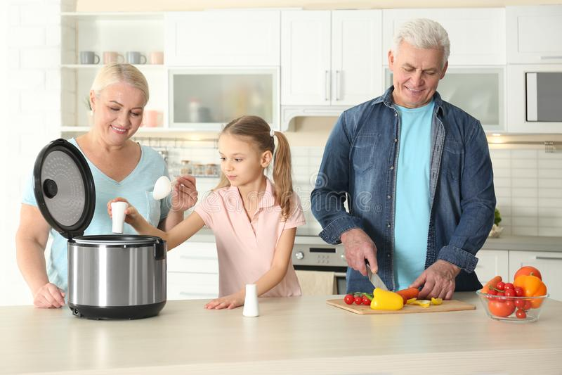 Dorośleć pary i ich wnuczki narządzania jedzenia z nowożytną wielo- kuchenką obrazy stock