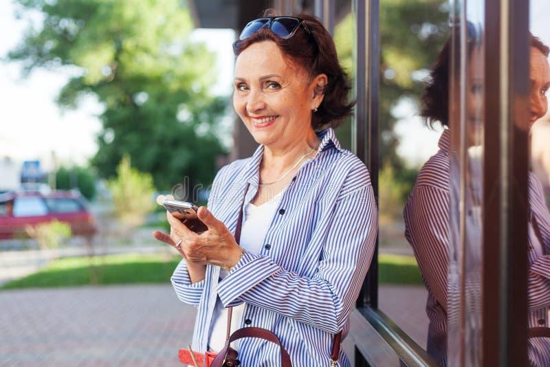Dorośleć atrakcyjnej eleganckiej kobiety przechodzić na emeryturę używać telefon komórkowego app obraz stock