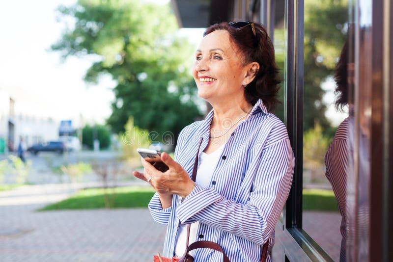 Dorośleć atrakcyjnej eleganckiej kobiety przechodzić na emeryturę używać telefon komórkowego app zdjęcie royalty free