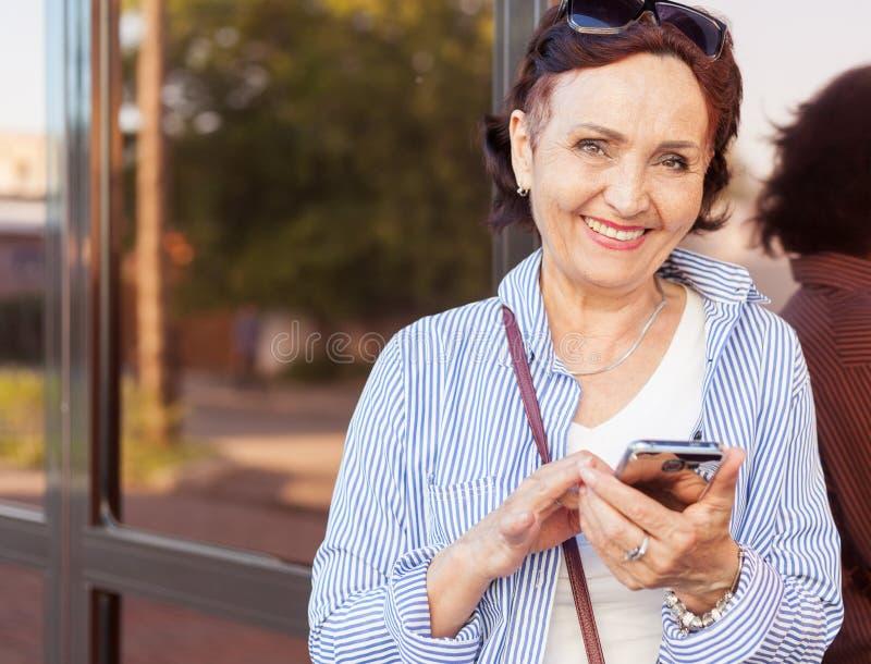 Dorośleć atrakcyjnej eleganckiej kobiety przechodzić na emeryturę używać telefon komórkowego app obrazy royalty free