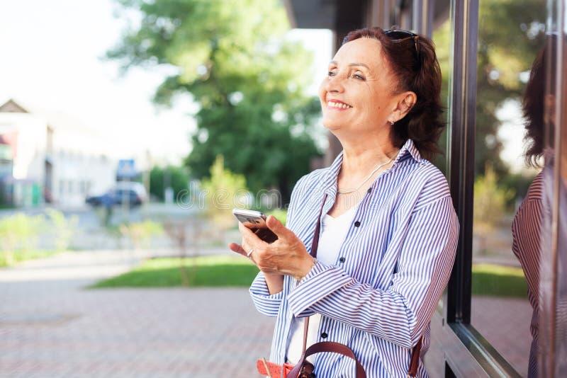 Dorośleć atrakcyjnej eleganckiej kobiety przechodzić na emeryturę używać telefon komórkowego app obraz royalty free