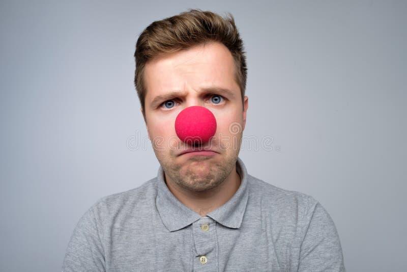 Dorośleć caucasian mężczyzny jest ubranym błazenu czerwonego nos odizolowywającego na szarym tle fotografia stock