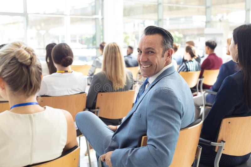 Dorośleć Kaukaskiego męskiego kierownictwa siedzącego w sali konferencyjnej, ono uśmiecha się kamera fotografia royalty free