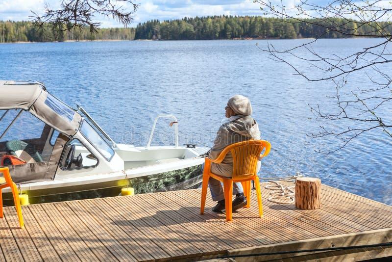 Dorośleć Kaukaskiej kobiety relaksuje przy jeziornym obsiadaniem na molu fotografia royalty free