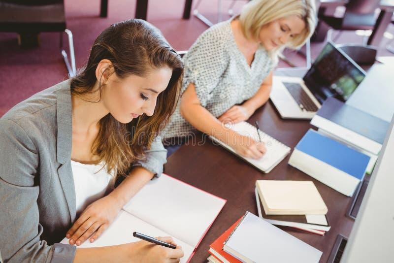 Dorośleć kobieta uczni pisze notatkach przy biurkiem obrazy royalty free