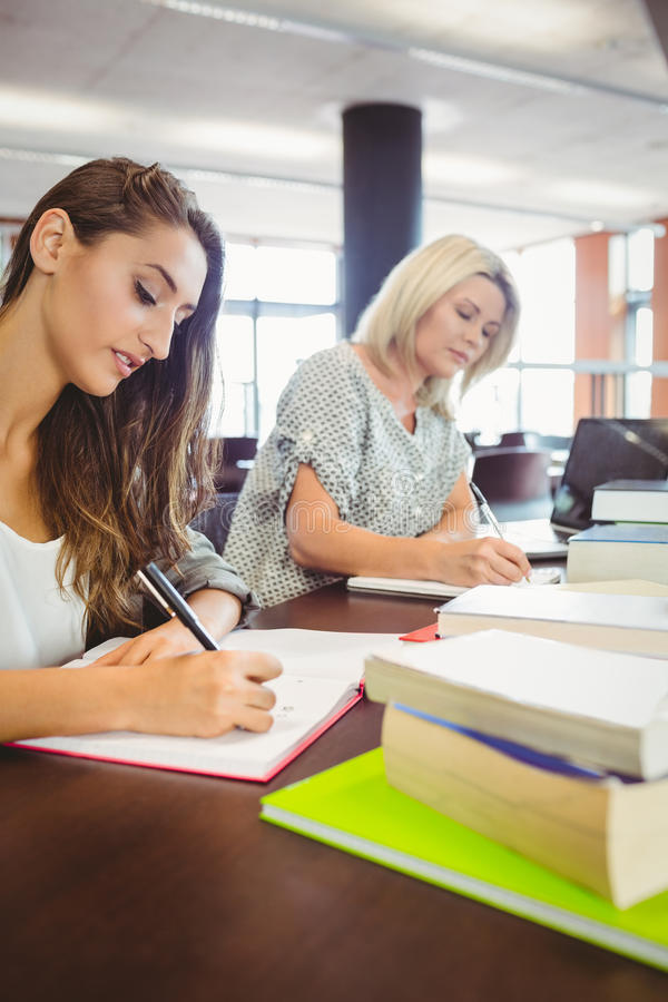 Dorośleć kobieta uczni pisze notatkach przy biurkiem zdjęcia royalty free