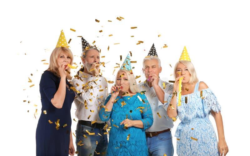 Dorośleć ludzi w przyjęcie urodzinowe kapeluszach z gwizd na białym tle fotografia royalty free