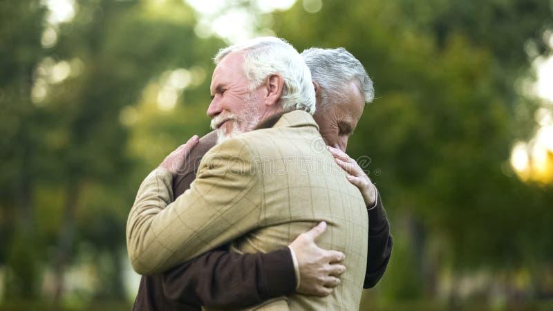 Dorośleć mężczyzn ściskać, szczęśliwy widzieć each inny, starych przyjaciół spotykać, wita obrazy stock