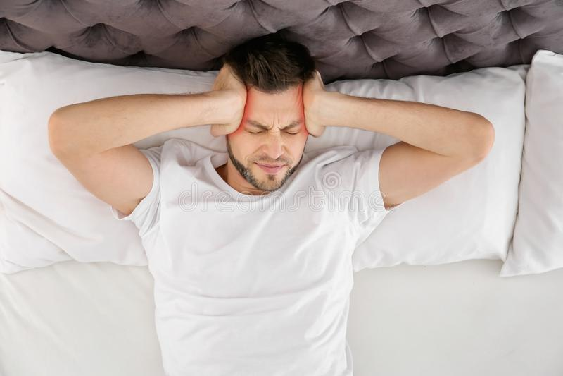 Dorośleć mężczyzna cierpienie od migreny na łóżku zdjęcia stock