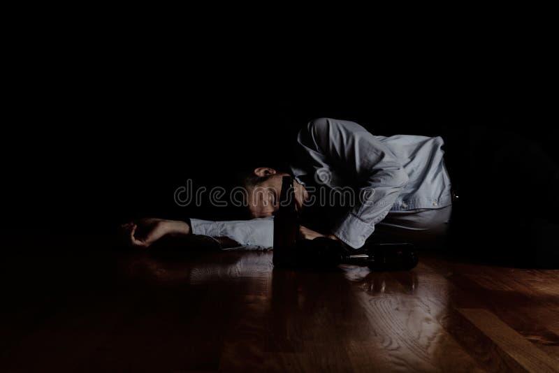 Dorośleć mężczyzna dosypianie na podłoga po pić zbyt dużo z ciemnym b obrazy royalty free