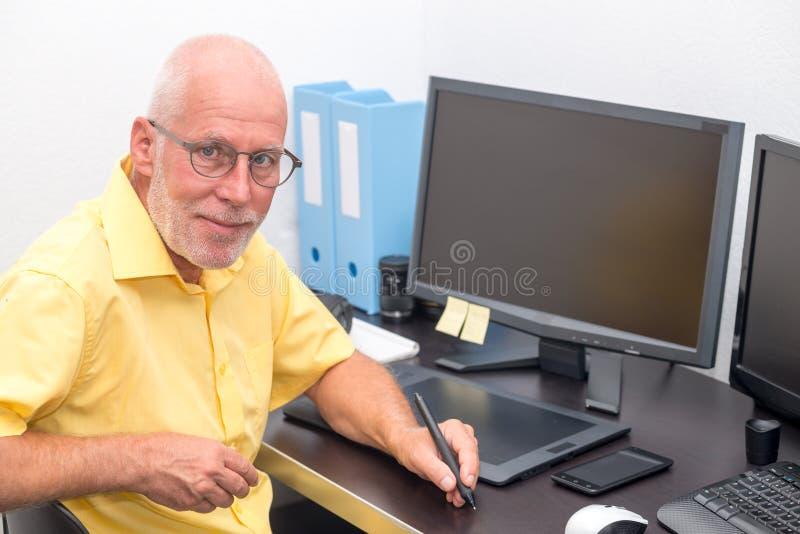 Dorośleć mężczyzna pracuje z grafiki pastylką w jego biurze zdjęcia stock
