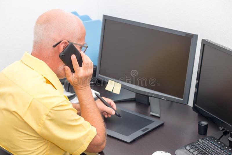 Dorośleć mężczyzna pracuje z grafiki pastylką w jego biurze obraz stock