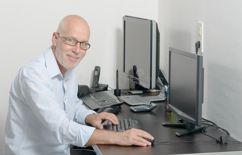 Dorośleć mężczyzna pracuje z jego komputerem fotografia royalty free