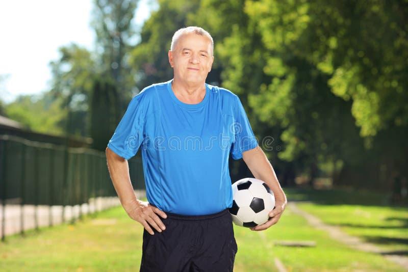 Dorośleć mężczyzna trzyma piłkę w parku w sportswear zdjęcia stock
