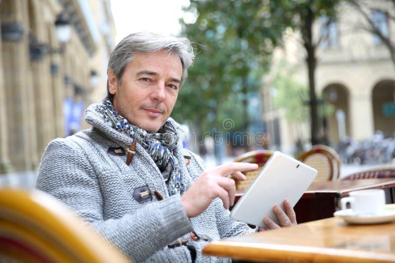 Dorośleć mężczyzna websurfing na pastylce w sklep z kawą zdjęcie royalty free