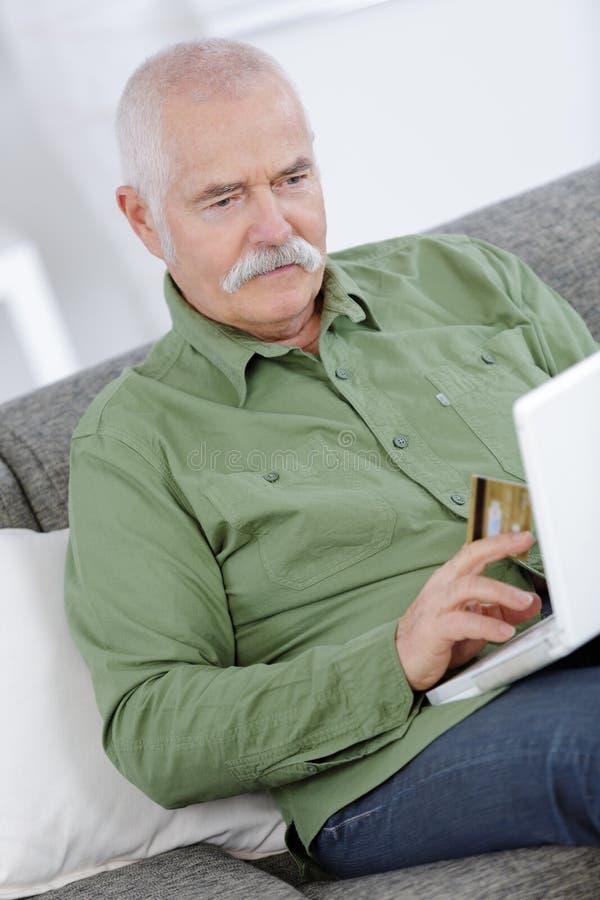 Dorośleć mężczyzna z szary twarzowy shoping na internecie zdjęcie royalty free
