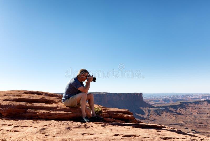 Dorośleć mężczyzny bierze fotografie Grand Canyon podczas gdy siedzący puszek zdjęcie royalty free
