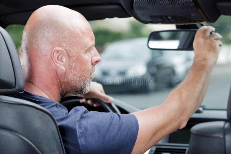 Dorośleć mężczyzny przystosowywa tylni widoku lustro w samochodzie zdjęcia stock