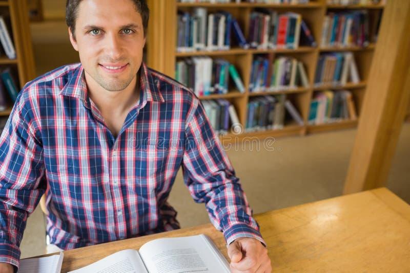 Dorośleć męskiego ucznia studiowanie przy biurkiem w bibliotece obrazy royalty free