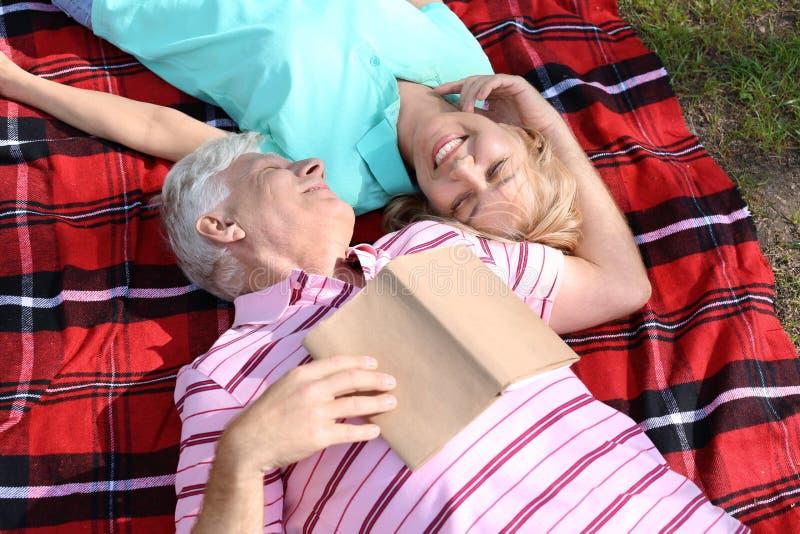Dorośleć pary czytelniczą książkę w parku na wiosna dniu fotografia stock