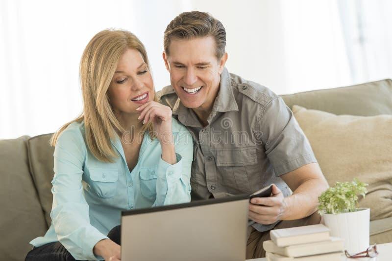 Dorośleć pary Używa telefon komórkowego I laptop Na kanapie obraz stock
