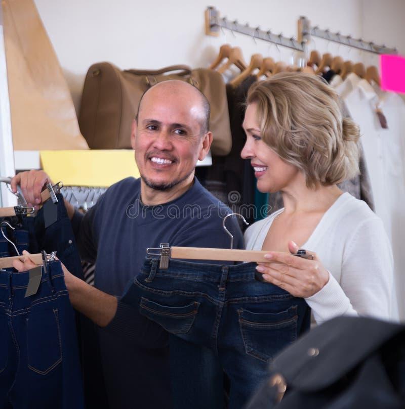 Dorośleć pary wybiera cajgi w sklepie obrazy royalty free