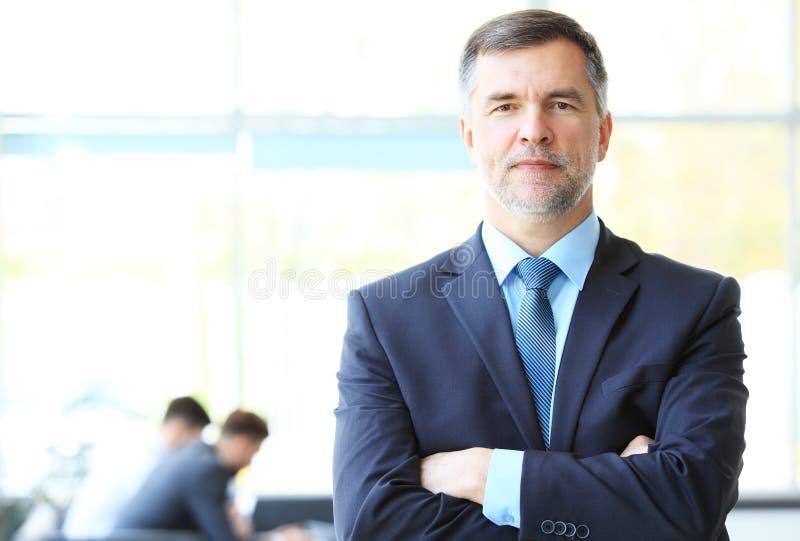 Dorośleć uśmiechniętego business manager krzyżuje jego ręki przed jego biznes drużyną obrazy stock