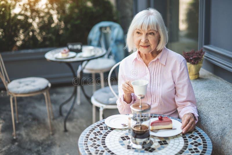 Dorośleć zadumanej kobiety pije herbaty w samotności outside zdjęcie royalty free