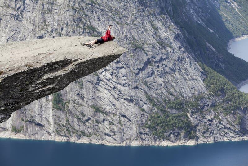 Dorośli leżą na skale Trolltunga i robią selfie smartfonem Klif jest w Oddzie, hrabstwie Hordaland, Norwegia zdjęcie stock