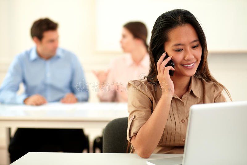 Dorosła asiatic kobieta conversing na jej telefonie komórkowym zdjęcie royalty free